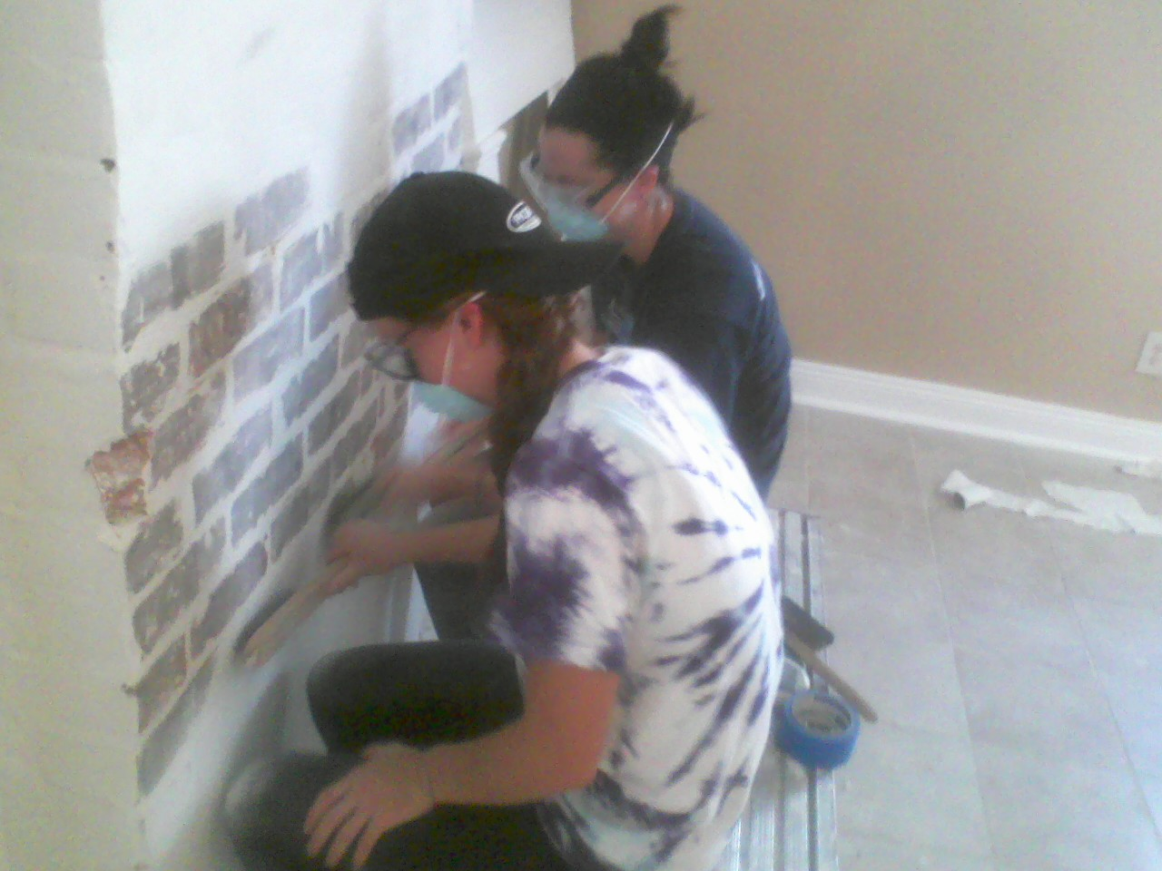 Lilla McMillan and Madison Smith sand the fireplace.