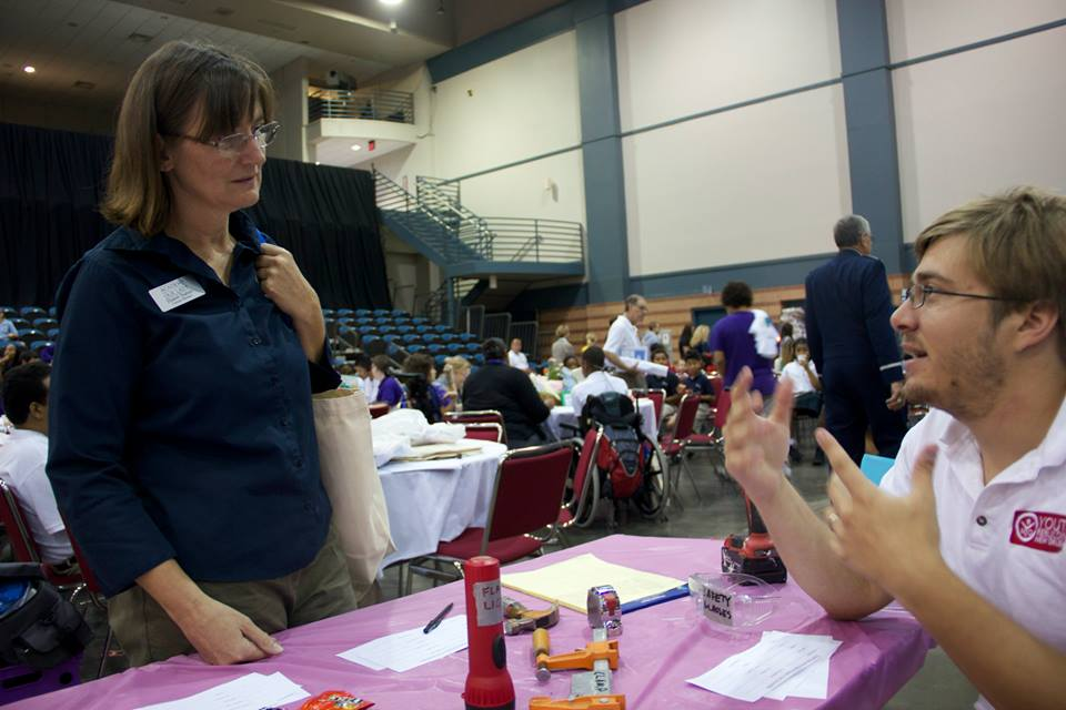 Will talks to one of the many teachers that stopped by the table.