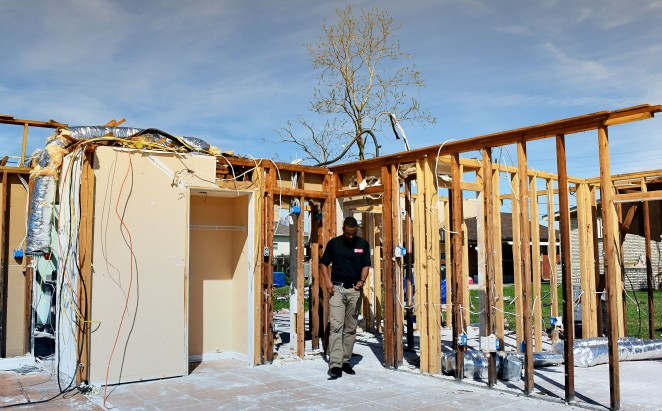 Prince walking through a home damaged by the tornado in New Orleans East